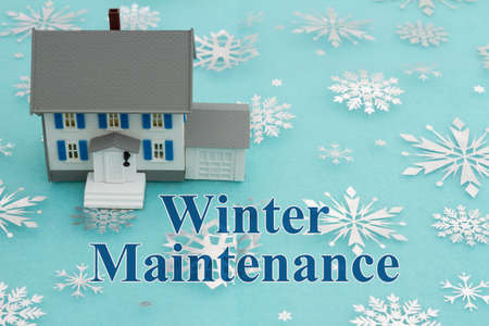 Winter Maintenance message with model house with blue and silver snowflakes Banque d'images
