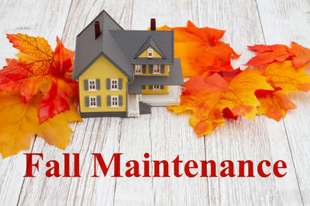 Fall Maintenance message with model house with fall leaves on weathered wood Banque d'images