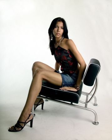 Sad but lovely young woman sitting on a black chair photo