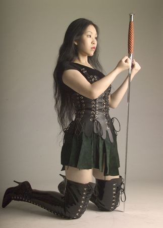 Warrior princess kneels to make a pledge with her sword photo