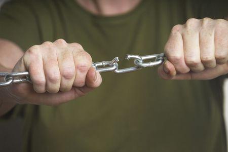 chainlinked: Vrouw breekt een keten Stockfoto