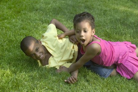 family tickle: Two kids playing in the park