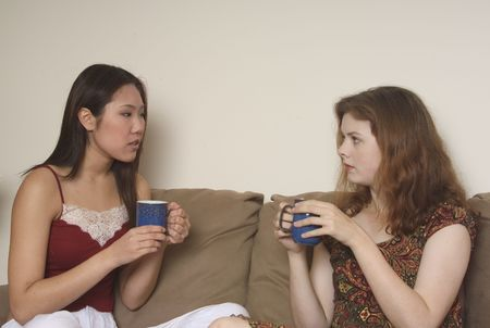 Two friends chat over a coffee at home