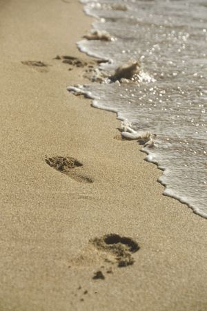 Foot prints at the edge of the sea Stock Photo