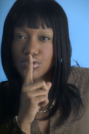 Girl with finger to her lips asking for quiet