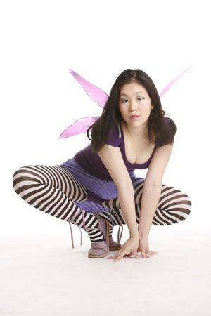 Fairy with wings crouching photo