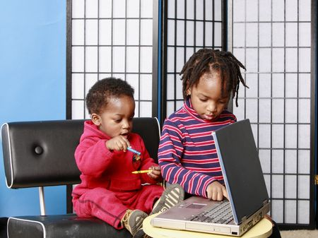 Two little boys playing with a computer photo