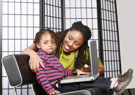 Smiling child with a lap top and his mother