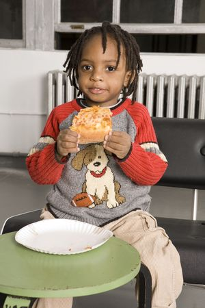 Little boy eating pizza photo