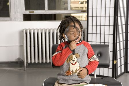 Child playing with a magnifying glass photo