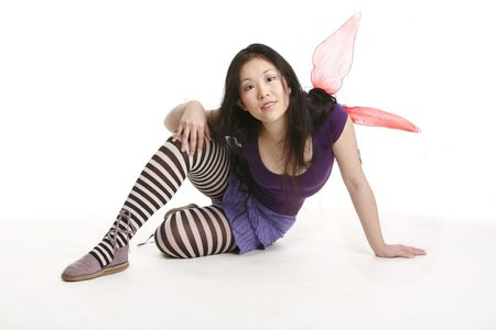 Smiling fairy sitting on the floor photo