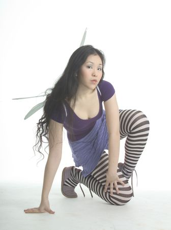 Pretty fairy in striped tights kneeling Stock Photo