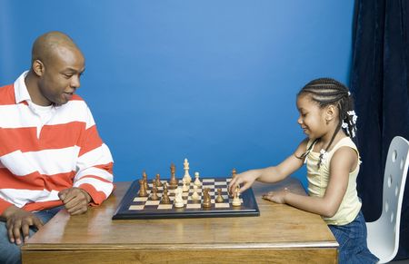 Dad teaching daughter to play chess