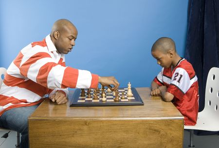 jugando ajedrez: Padre que juega a ajedrez con su muchacho Foto de archivo