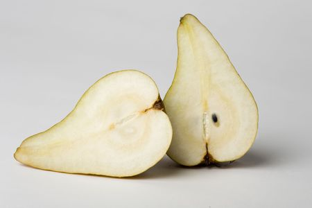 Juicy pear cut in half on a white background