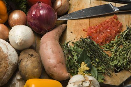 Root vegetables and herbs with a chopping board