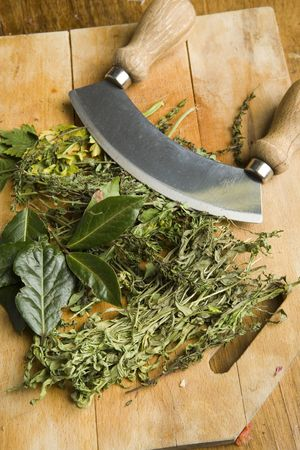 mincing: Various herbs with a mincing knife on a chopping board