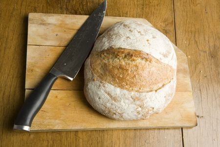 Traditional loaf with a knife on a chopping board