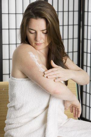 Woman using skin cream after a bath photo