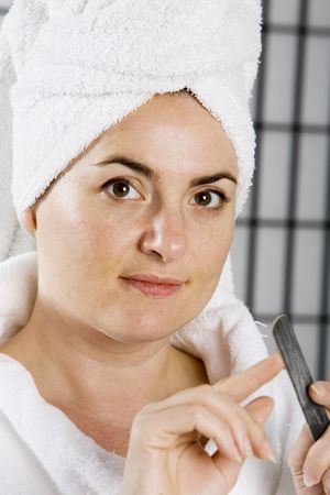 Woman in a bath robe filing her nails