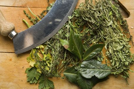 Various herbs with a mincing knife on a chopping board