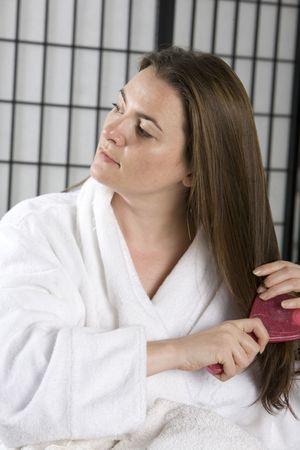 Pretty girl brushing her hair photo