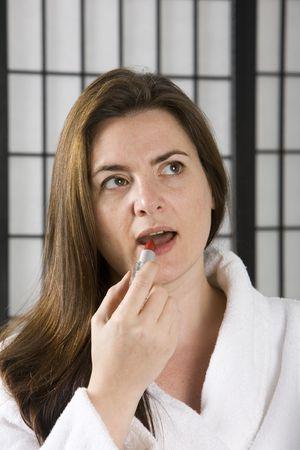 Woman puting on bright red lip stick