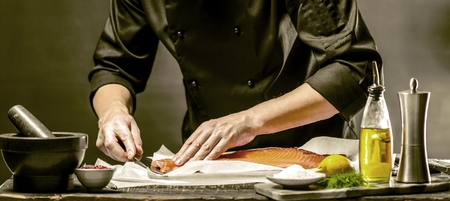 The big salmon is in the hands of the chef cook He is using a knife to slice salmon fillet