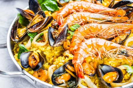 Traditional seafood paella in the pan on a wooden table 版權商用圖片