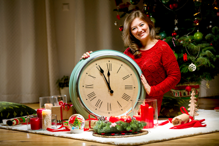 Portrait of a young girl in red  sweater with alarm clock at Christmas lights background 写真素材