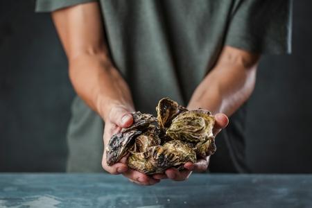 Fresh raw oysters in man hands on dark bakground Stock Photo