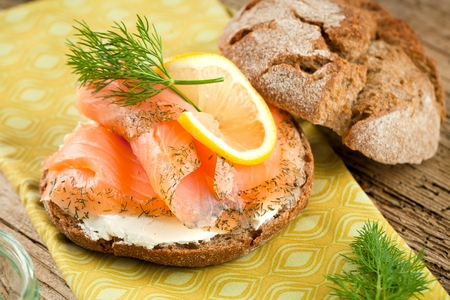 bread with fresh salmon fillet isolated on wooden background