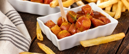 Traditional German currywurst, served with pommes on wooden background.