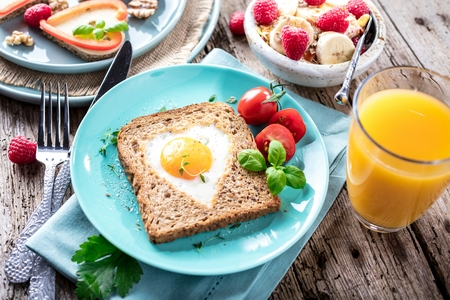 Breakfast on Valentines Day - fried eggs and bread in the shape of a heart and fresh vegetables.
