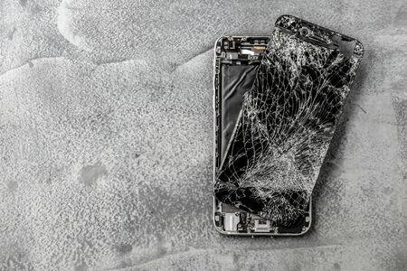 mobile phone with broken touchscreen on gray background. Reklamní fotografie - 147220843