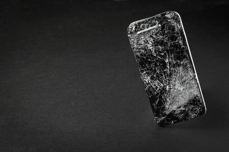 mobile phone with broken touchscreen on gray background. Reklamní fotografie