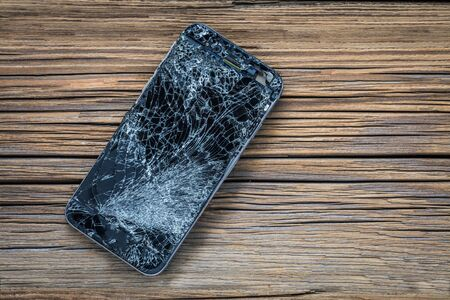 mobile phone with broken touchscreen on wooden background.