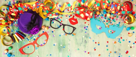 Colorful birthday or carnival frame with party items on wooden background Standard-Bild