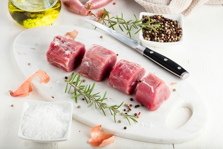 Pork fillet. Raw meat with spices on cutting board Imagens
