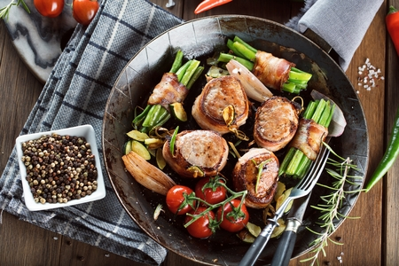 Juicy pork medallions wrapped in bacon, serve on the iron pan on the dark wooden dackground. Close up