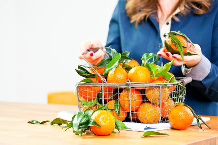Woman hands with iron basket with fresh clementine copy space