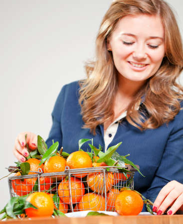 Woman hands with iron basket with fresh clementine copy space. Banco de Imagens - 151605271