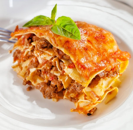 Tasty lasagne with meat covered with cheese served on white plate. Foto de archivo