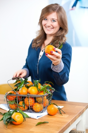 Woman hands with iron basket with fresh clementine copy space.