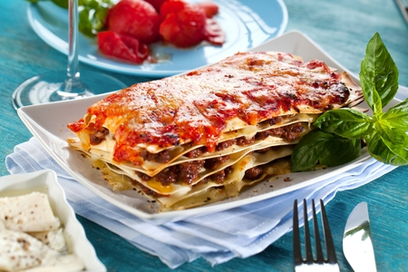 Tasty lasagne with meat covered with cheese served on white plate.