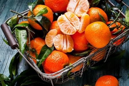 Fresh picked mandarins on wooden background closeup