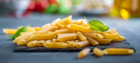 Fresh raw homemade fusilli and penne PASTA on Dark Table
