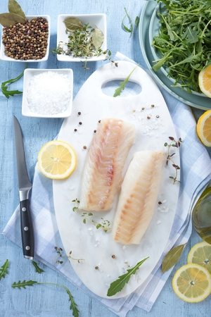 Fresh fish, raw cod fillets with addition of herbs and lemon Imagens