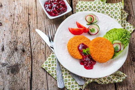 Breaded and baked camembert with cranberry sauce on wooden tabel Stock Photo