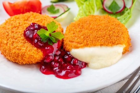 Breaded and baked camembert with cranberry sauce on wooden tabel Banco de Imagens